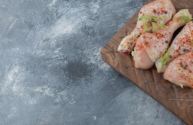 Chiuda sulla foto delle bacchette di pollo crude marinate sul tagliere di legno