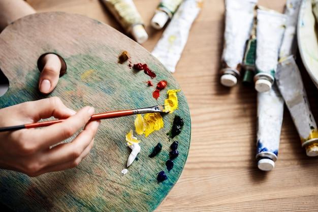 Chiuda sulla foto di miscelazione delle pitture ad olio sulla tavolozza