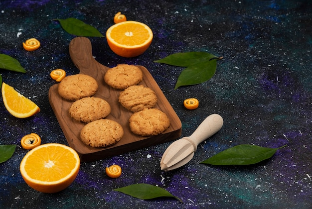 Close up photo o of homemade cookies on wooden chopping board and half cut oranges.