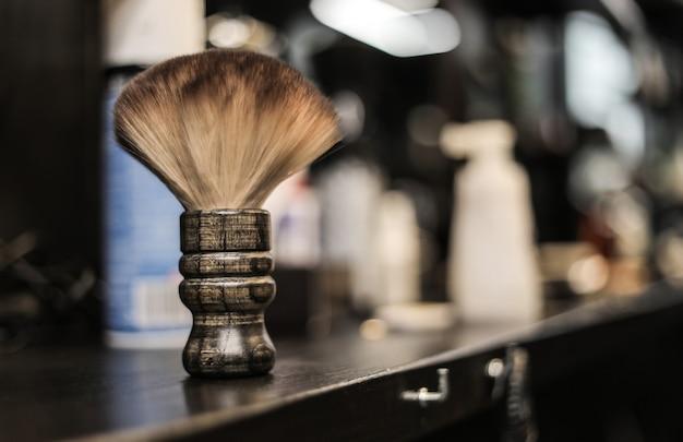 理髪店のカウンターに横たわっている、木製のブラシ、トリマー、はさみの理髪ツールキットの写真をクローズアップします。