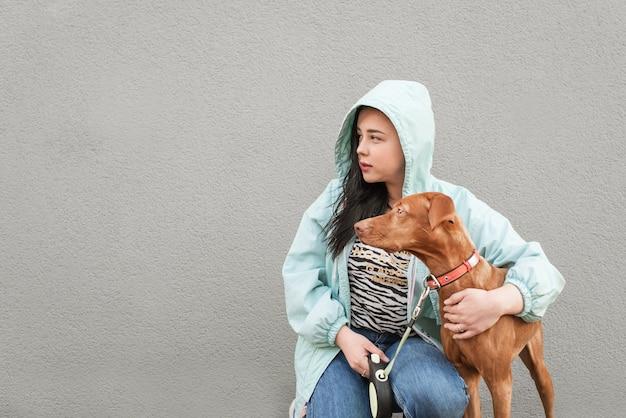Крупным планом фото красивой собаки и женщины на сером