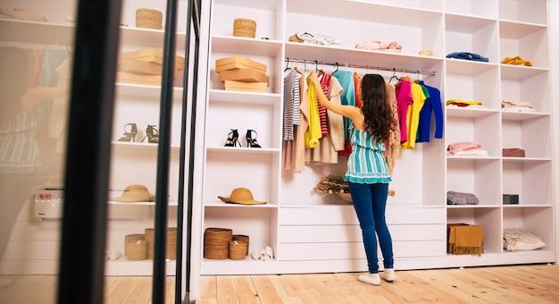 긴 밤색 머리를 한 아름다운 소녀가 카메라를 등지고 서서 큰 옷장에 있는 두 벌의 옷을 만지고 있는 클로즈업 사진.