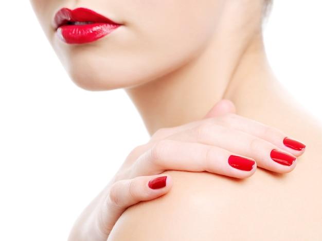 아름 다운 붉은 여성 입술의 클로즈업 사진입니다. 어깨에 미용 매니큐어와 손