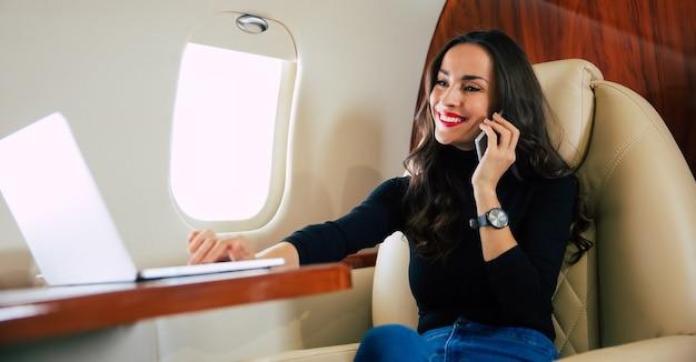 プライベートジェットでの飛行中に電話で話し、ブラックコーヒーを飲んでいるカジュアルな服装の美しい女性のクローズアップ写真。
