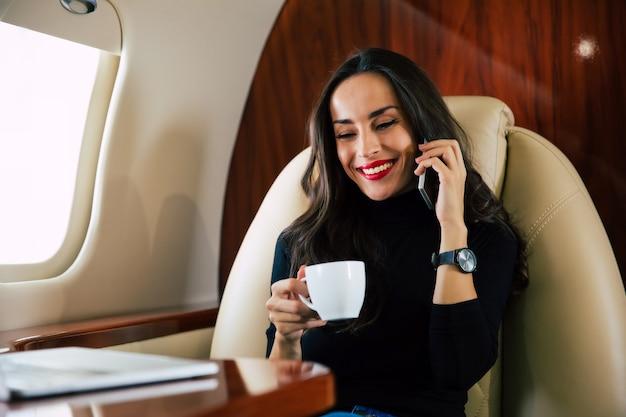 Крупным планом фото красивой женщины в повседневной одежде, которая разговаривает по телефону и пьет черный кофе во время полета на частном самолете.