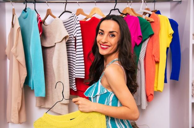 그녀의 큰 옷장 근처에 서서 두 개의 옷을 손에 들고 보고 선택하려고 하는 아름다운 여성의 클로즈업 사진.