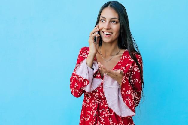 칠흑 같은 머리를 하고 빨간 여름 옷을 입고 전화 통화를 하면서 웃고 있는 아름다운 소녀의 사진을 클로즈업