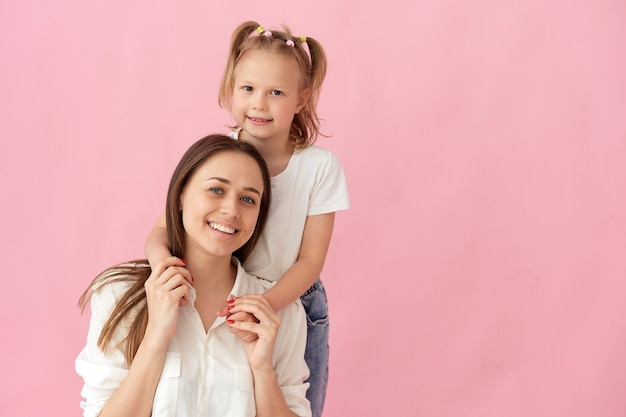 Крупным планом фото красивой молодой матери, обнимая ее маленькую дочь. объятия лучших друзей, искренние сердечные чувства, изолированные на пастельно-розовом фоне.