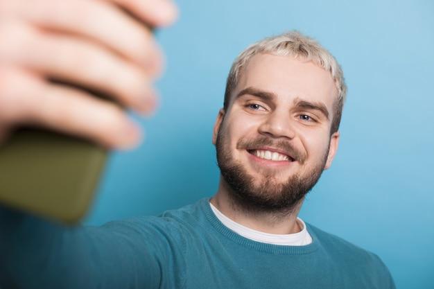 파란색 스튜디오 벽에 전화를 사용하여 셀카를 만드는 수염을 가진 금발 남자의 사진을 닫습니다