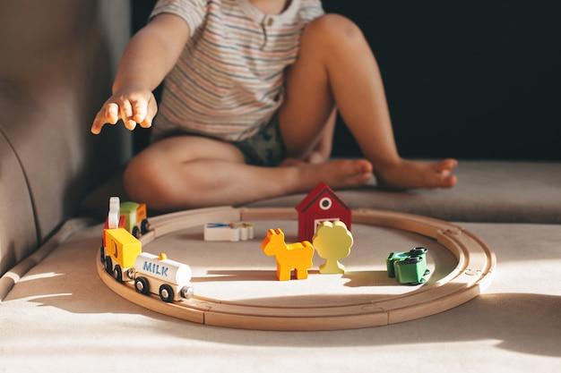 집에서 소파에 장난감 기차를 가지고 노는 소년의 사진을 닫습니다