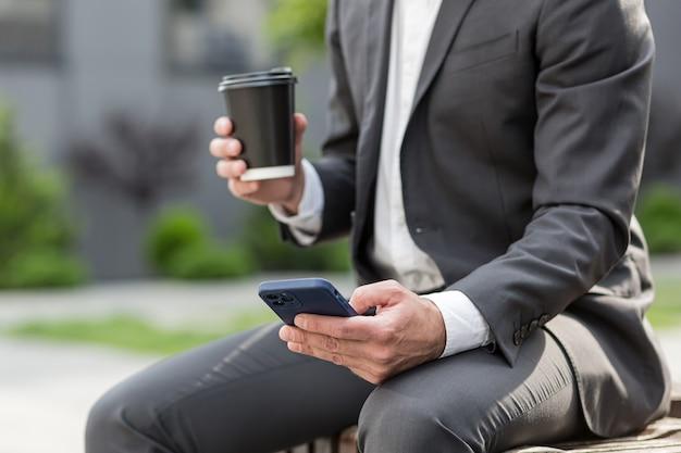 ビジネススーツ、カップと電話を持っている男の手で電話に対応するビジネスマンのクローズアップ写真