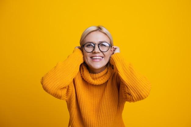 금발 머리와 안경이 그녀의 머리를 만지고 노란색 배경에 앞에 웃는 백인 여자의 사진을 닫습니다