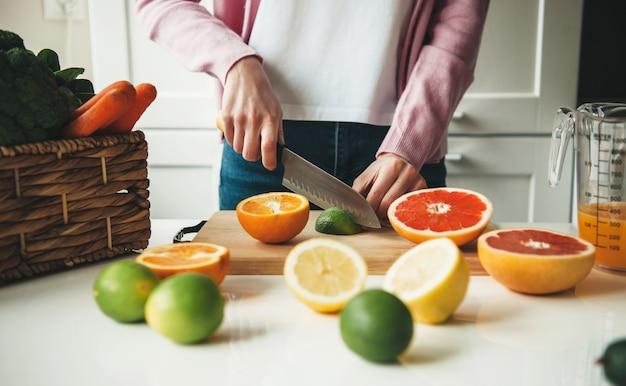 부엌에서 주스를 만드는 동안 과일을 자르는 백인 여자의 사진을 닫습니다