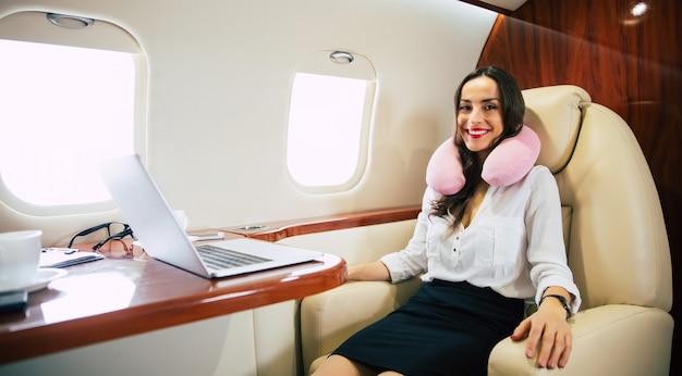 ビジネスクラスの航空機の窓際の席で昼寝をしている白いブラウスを着た魅力的な女性のクローズアップ写真。