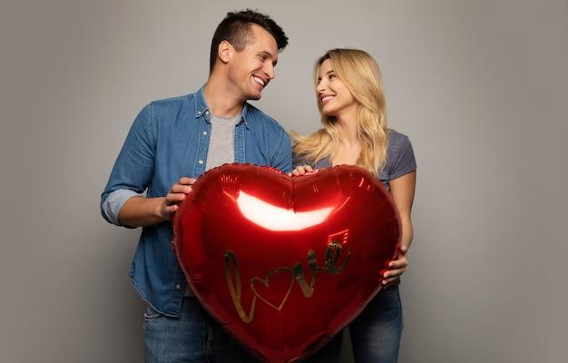 Фотография крупным планом веселой пары в повседневной одежде, которые держат вместе большой воздушный шар в форме сердца, улыбаются и смотрят друг другу в глаза.