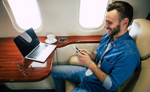 フライトを楽しんでいる、窓際の席に座ってスマートフォンでメッセージを交換しているカジュアルな服装の陽気な男性のクローズアップ写真。