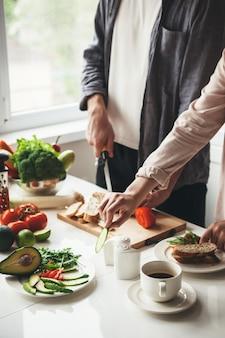 빵과 야채를 자르는 부엌에서 함께 아침 식사를 준비하는 부부의 사진을 닫습니다