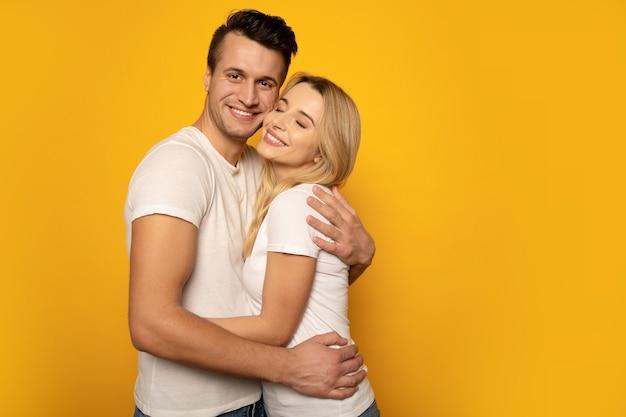 Крупным планом фото милая пара, крепко обнимающаяся и улыбающаяся, позирующая на желтом фоне