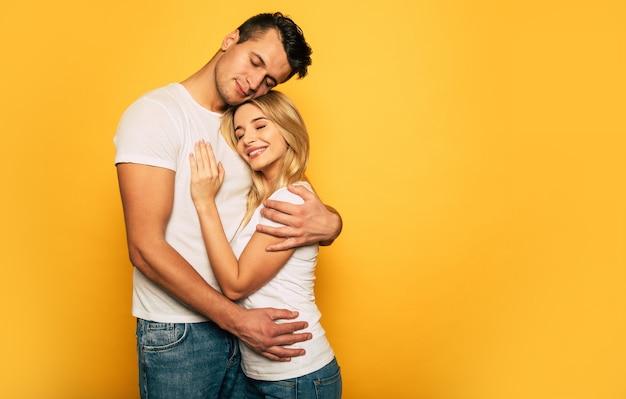 黄色の背景にポーズをとって、しっかりと抱き締めて笑っているかわいいカップルのクローズアップ写真