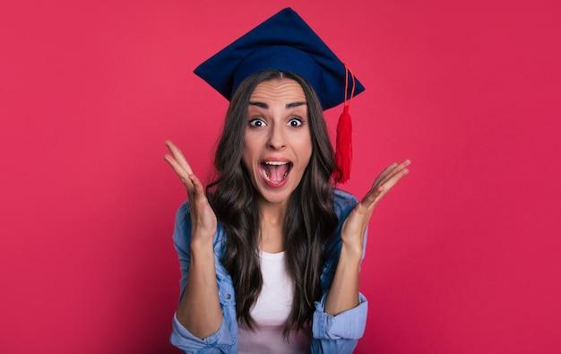 ブラウスと四角いアカデミックハットを着たかわいい学生のクローズアップ写真。彼女は大喜びし、彼女の成功を喜んで叫びます。