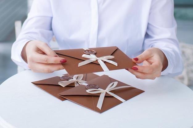 ワックスシール付きのブロンズ招待状の封筒を保持している女性の手のクローズアップ写真