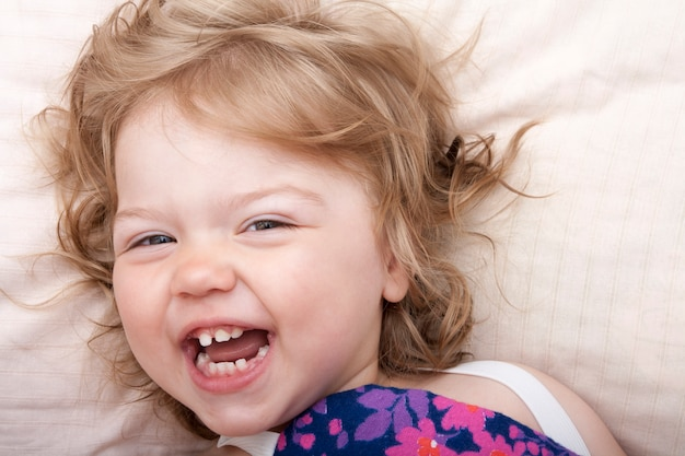 Крупным планом фото забавного веселого ребенка на подушке с