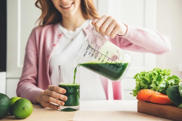 Крупным планом фото имбирной женщины, наливающей свежий зеленый сок в стакан