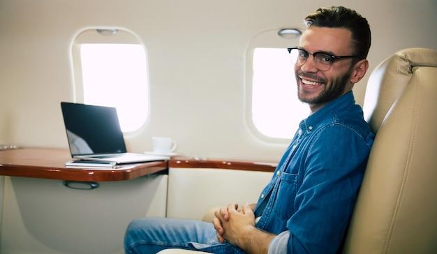 캐주얼 복장을 한 잘생긴 남자가 노트북에 무언가를 입력하고 왼손에 스마트폰을 들고 웃고 있는 클로즈업 사진은 일등석 비행기를 타고 있습니다.
