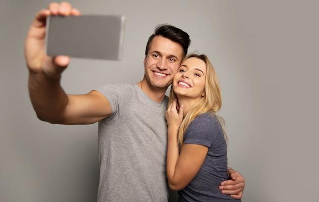 ゴージャスな女の子とカジュアルな服装の魅力的な男性のクローズアップ写真。彼らは一緒にセルフィーを撮りながら抱き合っています。