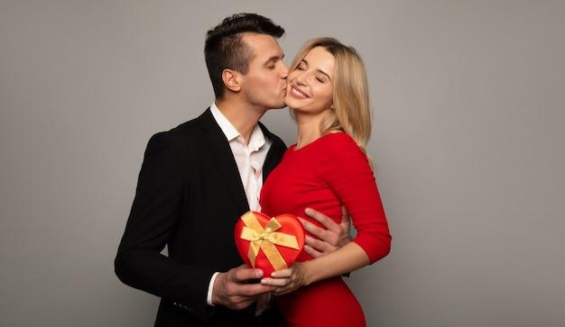 赤いドレスを着たゴージャスな女の子と黒いスーツを着た魅力的な男性が、プレゼントボックスを持って抱きしめ、カメラを見て、笑っている写真をクローズアップします。