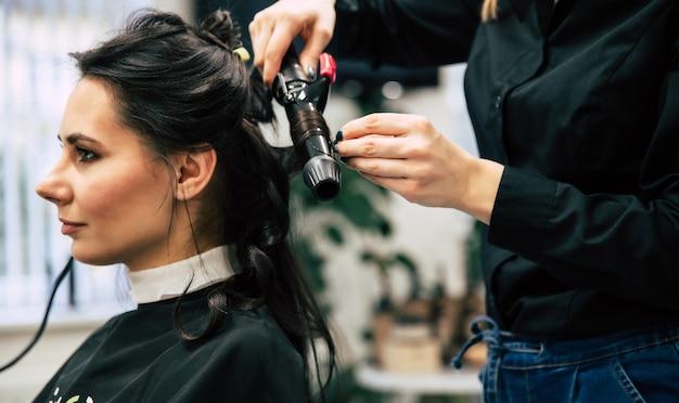 Крупным планом фото великолепной женщины с красивыми волнистыми волосами, делающей прическу в салоне красоты.