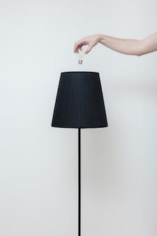 Фотография крупным планом. рука меняет лампочку в стильной лампе в стиле лофт с верхней стороны. лампа со спиральной нитью. современный яркий интерьер.
