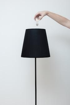 손의 클로즈업 사진은 상단에서 세련된 로프트 램프의 전구를 변경합니다.