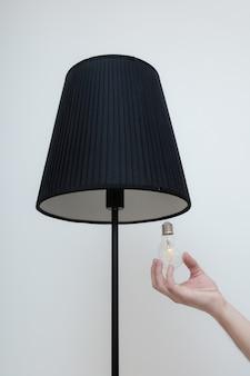 Фото крупным планом рука меняет лампочку в стильной лампе на чердаке. лампа со спиральной нитью. современный яркий интерьер.