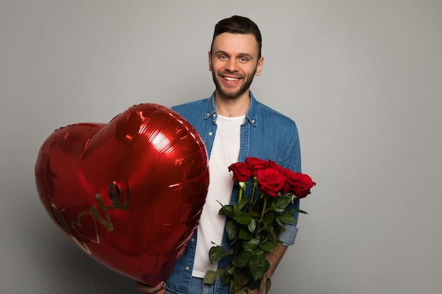 Крупным планом фото красивого мужчины, который смотрит в камеру, держит большой красный воздушный шар в форме сердца и букет роз и улыбается.