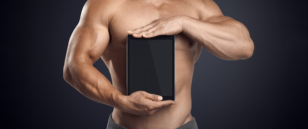 Крупным планом фото красивой молодой фитнес мужской модели без рубашки, держащей вертикально цифровой планшет с ...