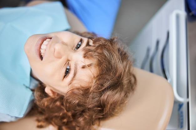 치과 의자에 누워있는 동안 그의 목에 생리대를 입고 행복한 소년의 근접 사진