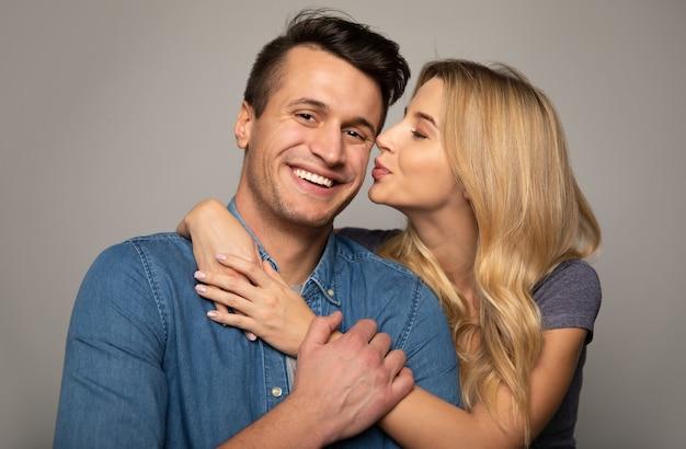 幸せから抱き合って笑っているカジュアルな服を着た幸せなカップルのクローズアップ写真。