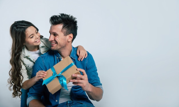 Фотография крупным планом счастливого отца в джинсовой одежде, улыбающегося, когда он получает подарок от своего любимого ребенка, который смотрит с нежностью