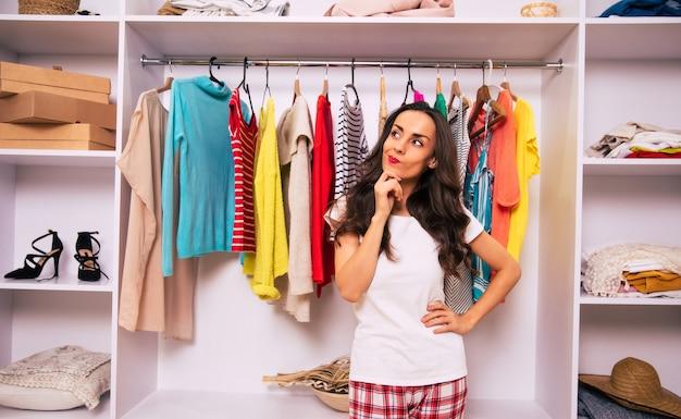 잠옷을 입은 행복한 소녀가 옷으로 가득 찬 큰 옷장 앞에 서서 어떤 옷을 입을지 고민하는 클로즈업 사진입니다.