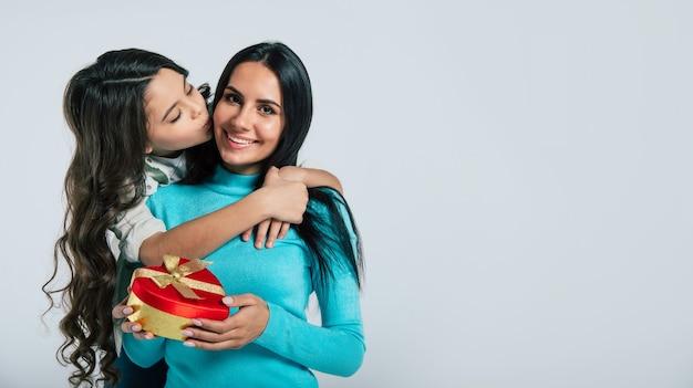 Фотография крупным планом счастливой матери, которая наслаждается подарком, который только что подарила ей ее маленькая дочь. обе смотрят друг на друга и улыбаются. Premium Фотографии