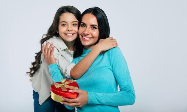 Фотография крупным планом счастливой матери, которая наслаждается подарком, который только что подарила ей ее маленькая дочь. обе смотрят друг на друга и улыбаются.
