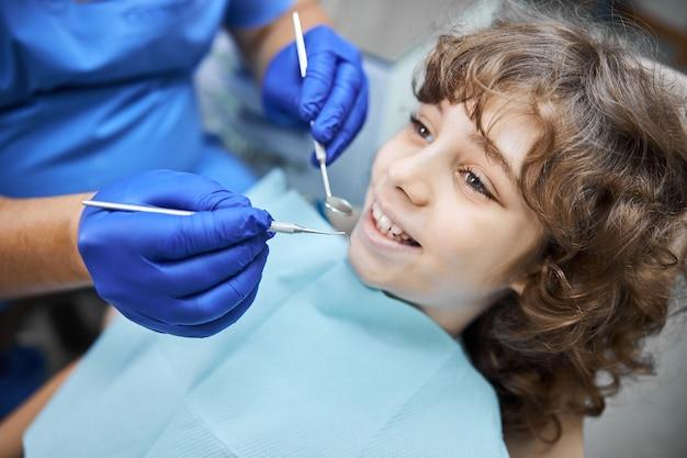 충치를 확인하기 위해 치과 거울이있는 치과 의사를위한 사랑스러운 아이의 입을 여는 근접 사진