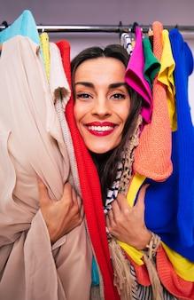 그녀의 얼굴만 보이도록 옷장에 걸려 있는 옷들을 껴안고 카메라를 바라보고 있는 큰 미소의 사랑스러운 여성의 클로즈업 사진.
