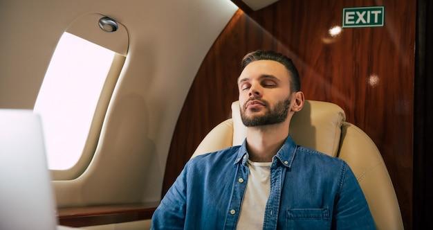 ファーストクラスの飛行機のボードの窓際の席に座って、目を閉じてリラックスしている、カジュアルな服を着た男性のクローズアップ写真。