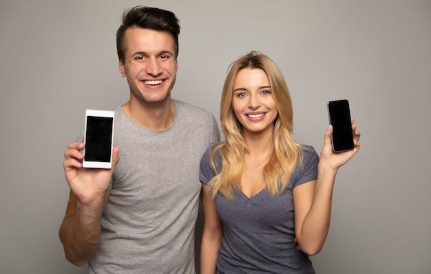Крупным планом фото супружеской пары из двух молодых людей, которые стоят впереди и улыбаются, показывая смартфоны в руках на камеру.