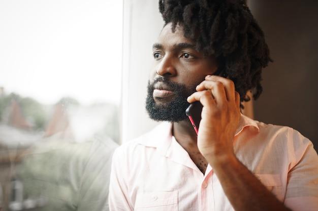 Крупным планом фото темнокожего мужчины средних лет в строгой рубашке, говорящего по телефону возле окна
