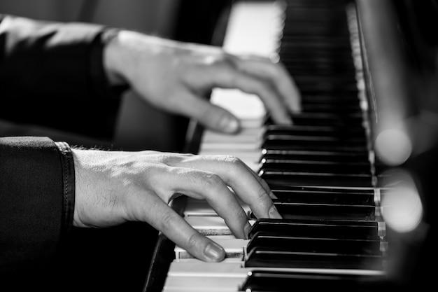 피아노 키보드를 연주하는 음악가의 사진을 닫습니다