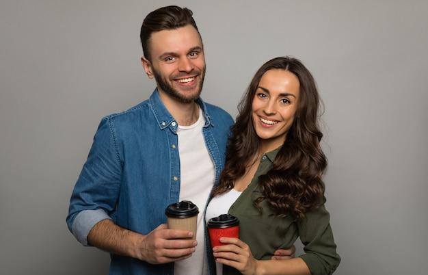 긴 밤나무 머리를 한 멋진 소녀의 클로즈업 사진은 수염을 기른 잘생긴 남자가 포옹하고 두 개의 커피 컵을 들고 서로를 상냥하게 바라보고 있습니다.