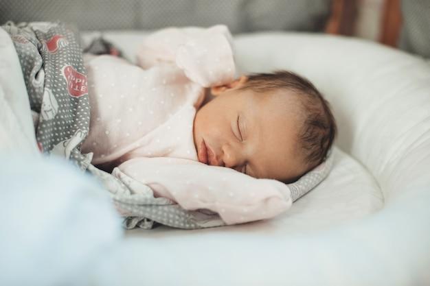 그녀의 침대에서 이불로 덮여 따뜻한 옷을 입고 잠자는 신생아의 사진을 닫습니다